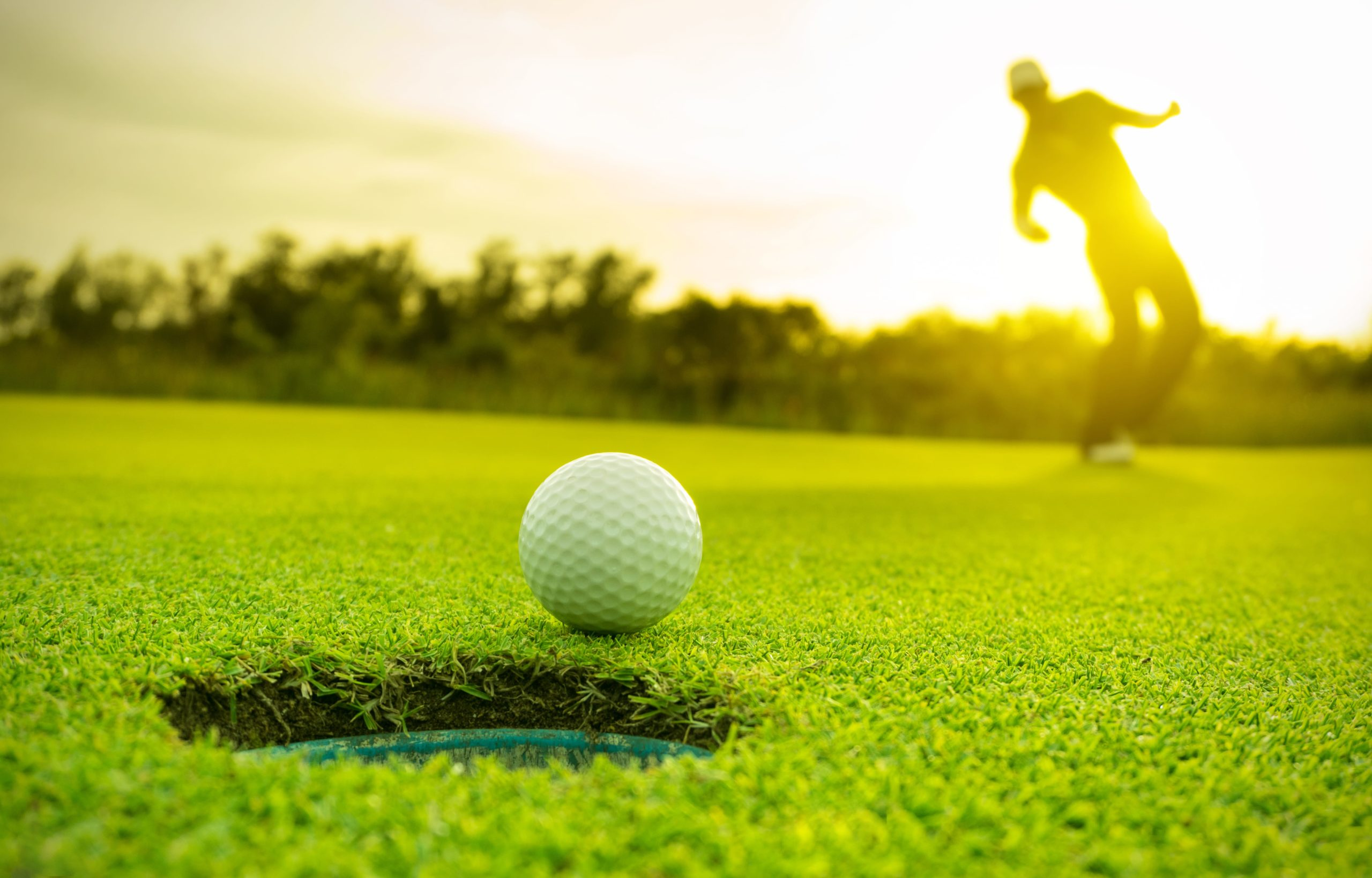 Golfer making a long putt on the green