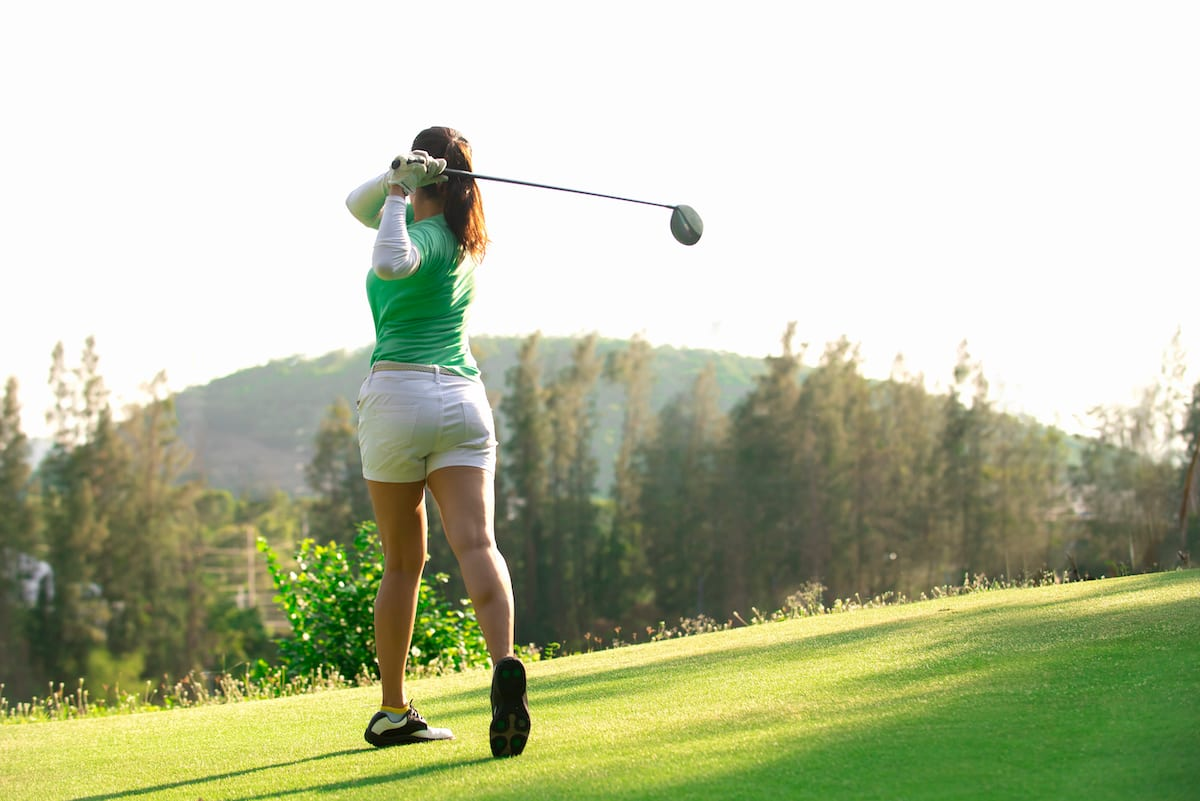 Woman taking a swing on the golf course