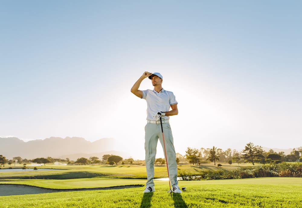 Golfer standing on course